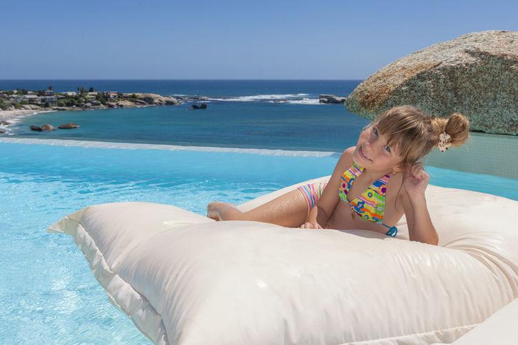 Portrait of girl wearing bikini lying on pool raft in infinity pool against clear blue sky