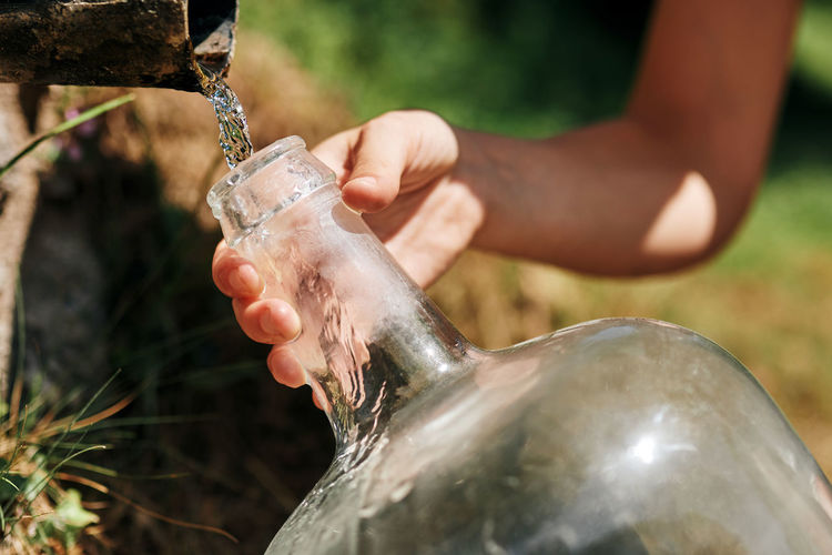 Close-up of hand pouring water