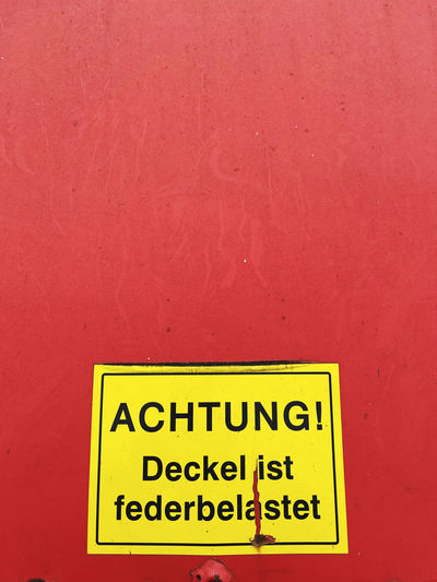 Close-up of warning sign on red wall