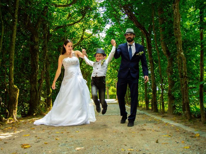 Full Length Of Bride And Bridegroom With Son Walking On Footpath