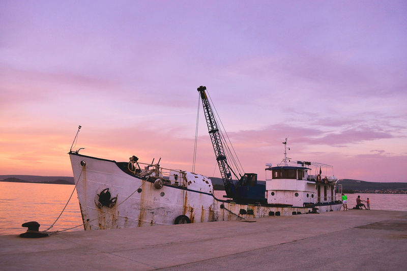 Fishing boat moored in river at harbor against cloudy sky at dusk