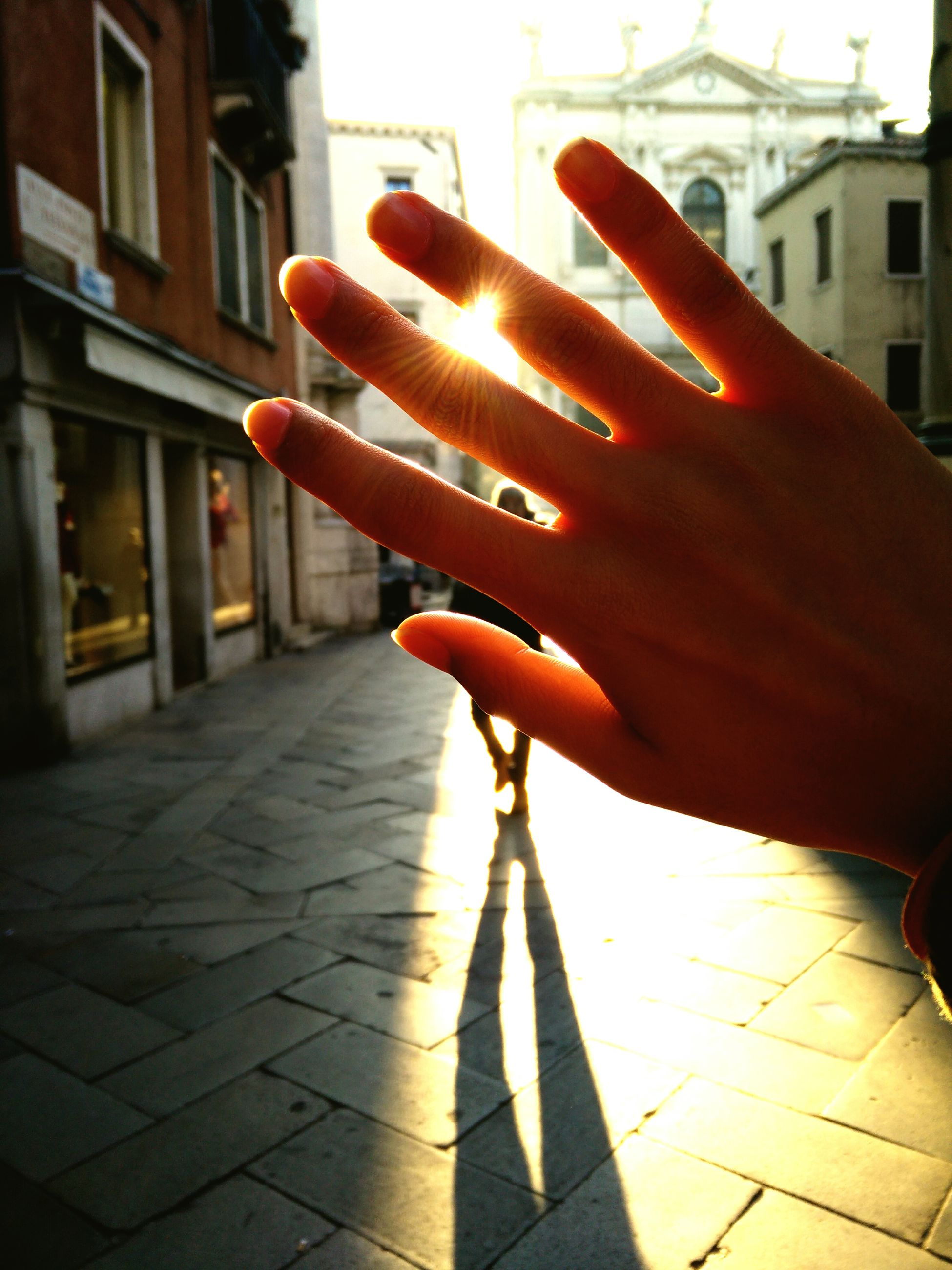 person, building exterior, architecture, built structure, lifestyles, men, street, holding, unrecognizable person, part of, cropped, leisure activity, orange color, sunlight, city, human finger