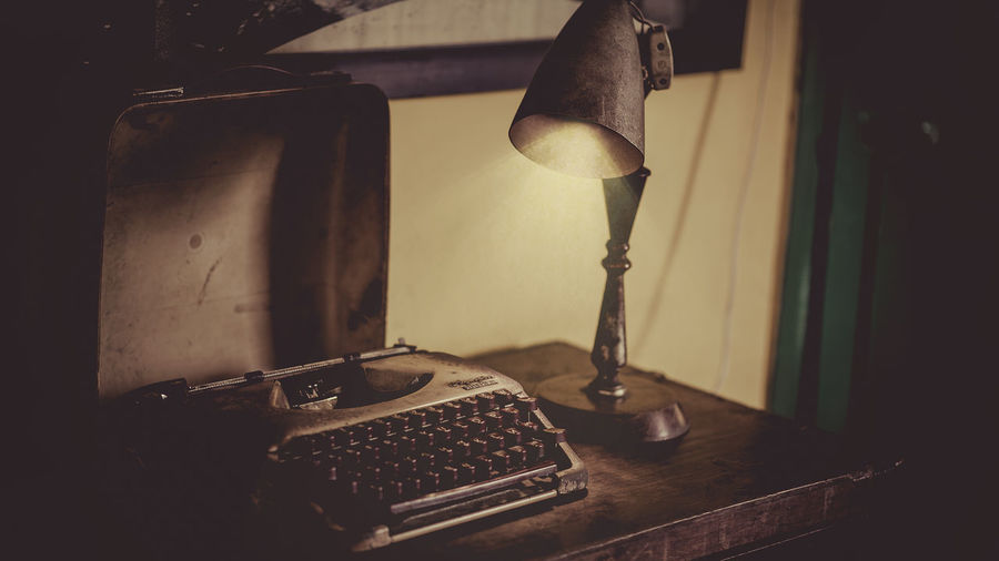 Close-up of old lamp and typewriter on table