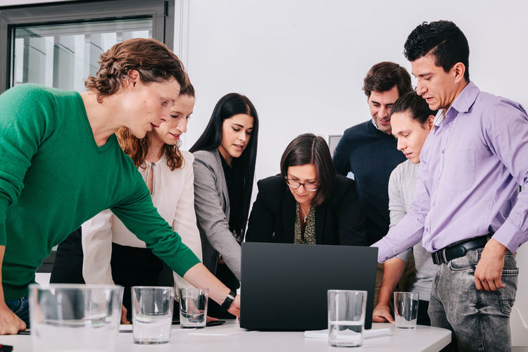 Coworkers working while standing by conference table