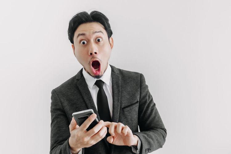 Man holding smart phone against white background
