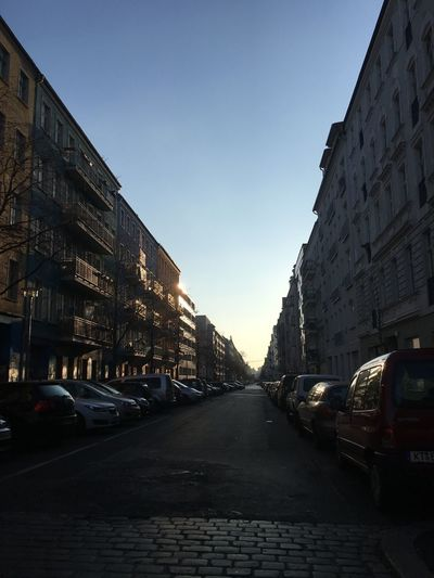 Cars on road amidst buildings against sky in city
