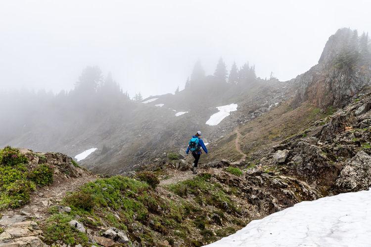Man riding on mountain against sky
