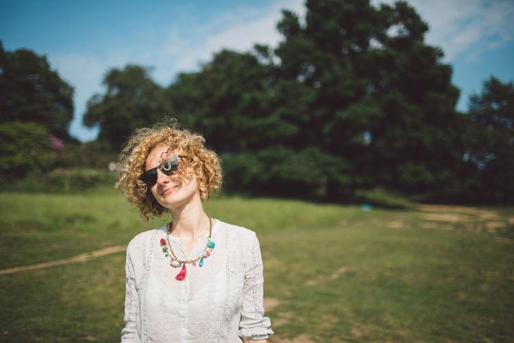 Portrait Of Woman In Sunglasses Standing On Field