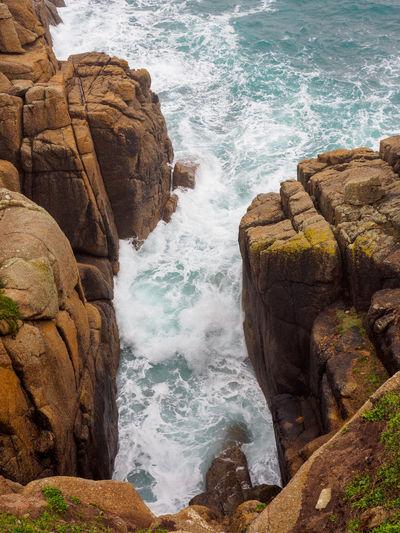Waves crash between the prismatic granite cliffs of porthcurno beach. cornwall, united kingdom.