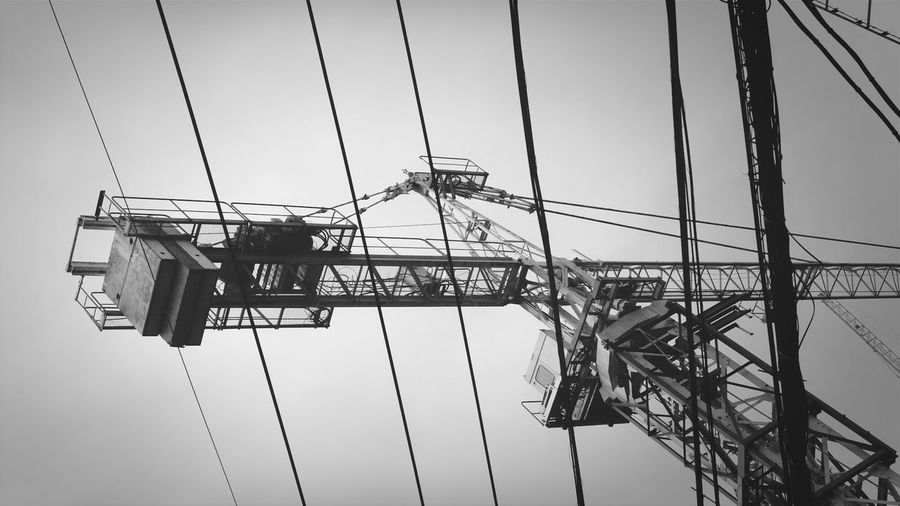 Low Angle View Of Crane And Cables Against Sky
