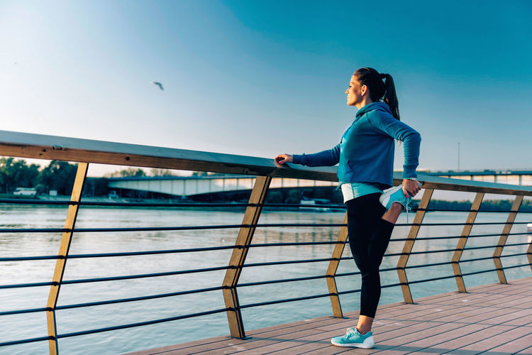 City City Life Exercising Girl Power Lifestyle One Person Only Riverside Sunlight Woman Blue Fit Fitness Healthy Lifestyle Outdoors Sporty Strength Stretching Sunset Urban