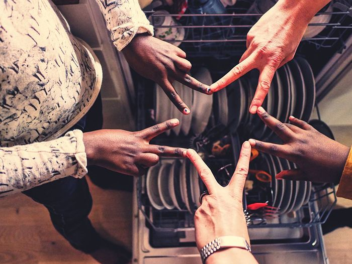 High angle view of friends making star shape with hands over plates in dishwasher
