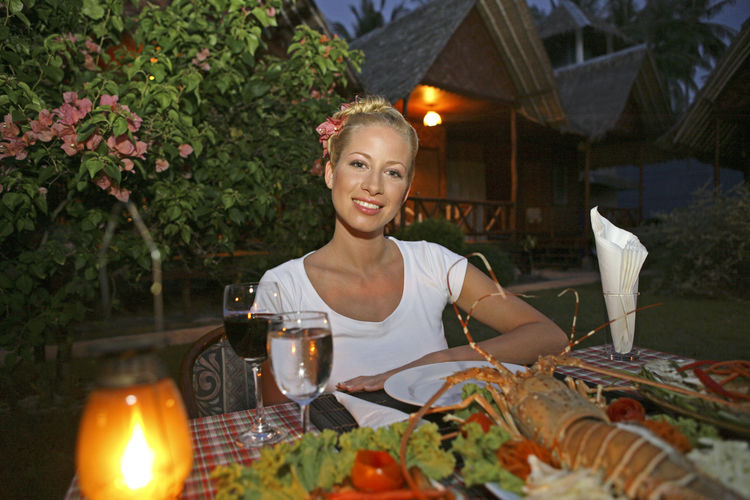 Portrait of young woman having meal at table in resort