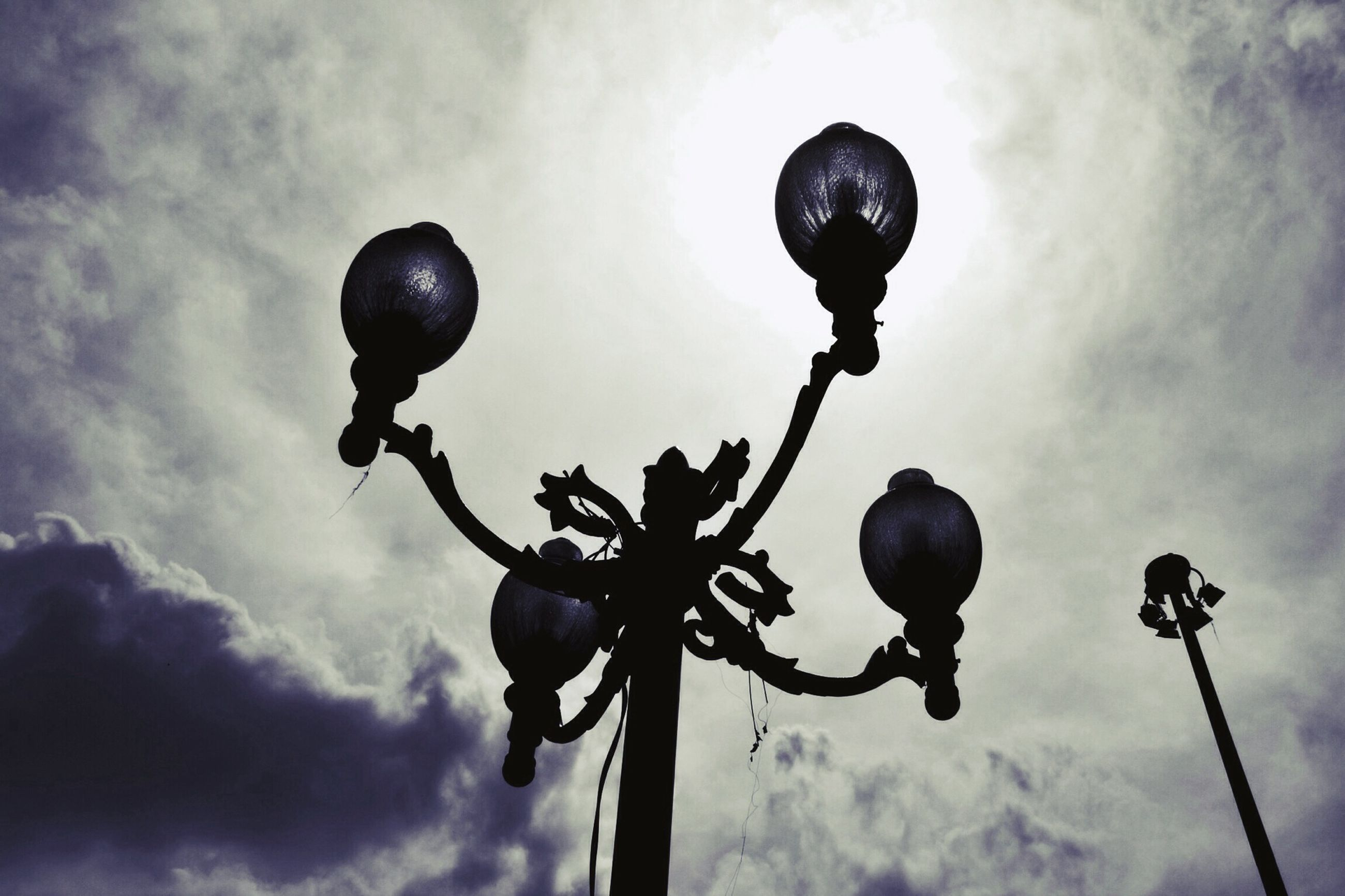 low angle view, sky, street light, lighting equipment, cloud - sky, silhouette, cloudy, cloud, outdoors, dusk, no people, hanging, electricity, day, sphere, nature, lamp post, metal, tree, connection