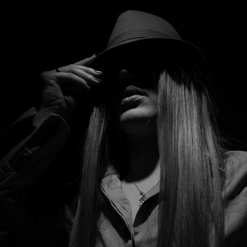 Low angle view of women with long hair wearing hat in darkroom