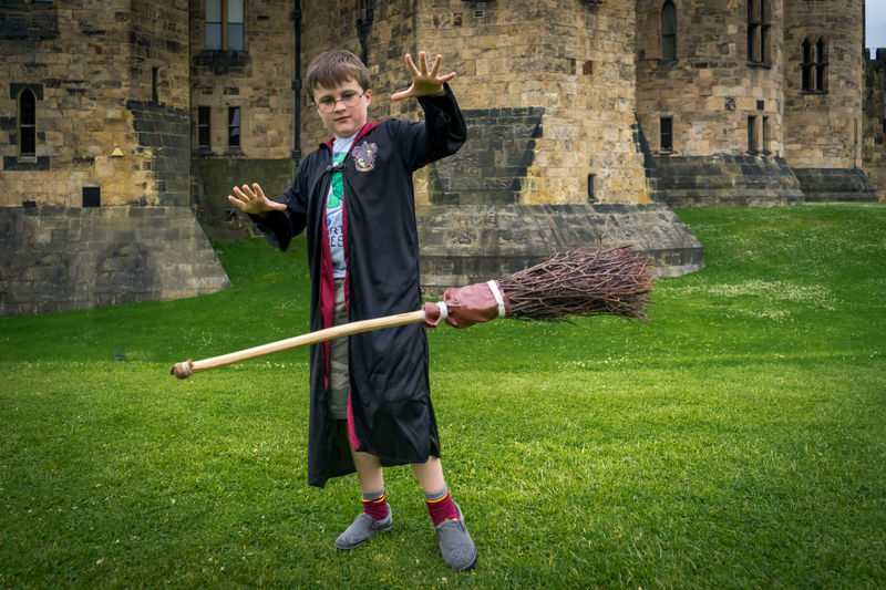 Arms Outstretched Broom Casual Clothing Day Focus On Foreground Full Length Grass Green Color Harrypotter Innocence Leisure Activity Lifestyles Magic Outdoors Person Playing Standing Wizard Young Adult