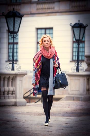 Young girl coming back after work. In background Fryderyk Chopin museum building