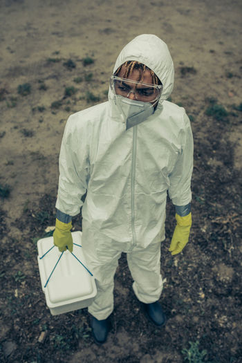 High angle view of man wearing protective suit holding basket standing outdoors