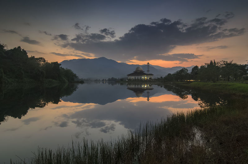 Darul quran mosque and lake against dramatic cloudy sky during sunrise