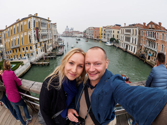 Portrait Of Smiling Couple Standing On Footbridge Over Canal