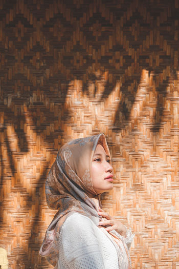 Side view of woman in hijab standing against patterned wall outdoors