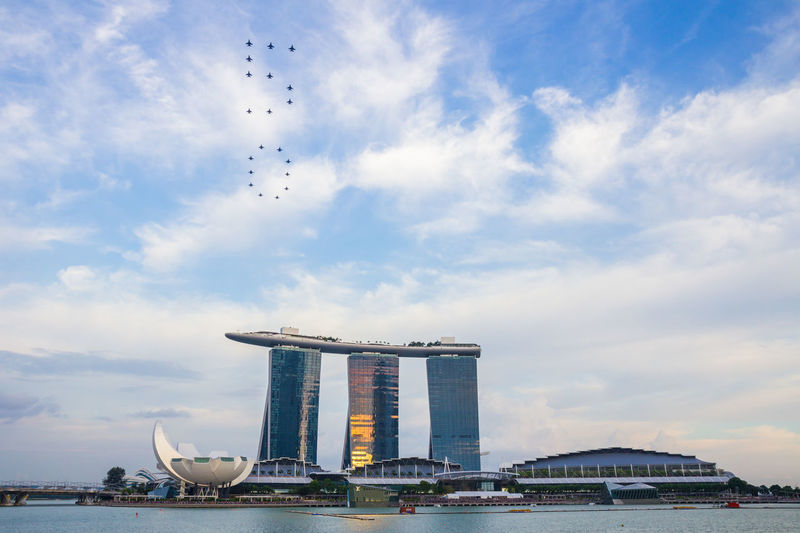 Low angle view of airshow over marina bay sands and river
