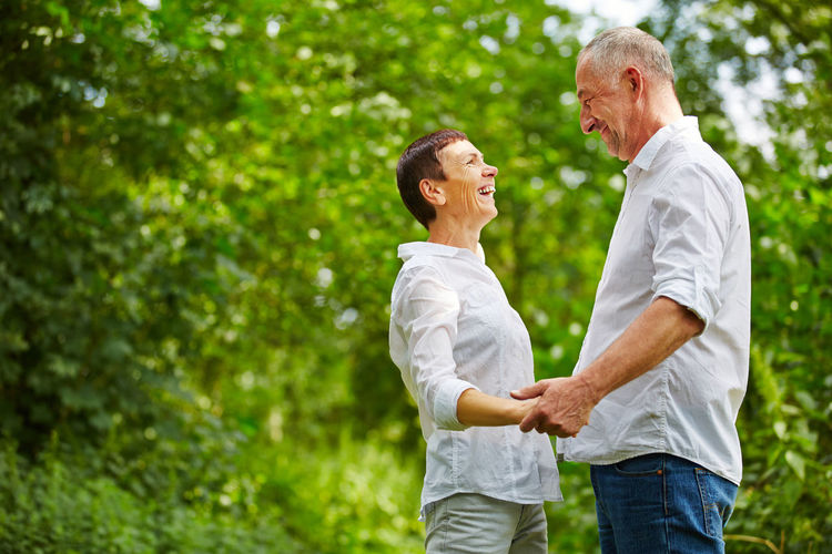Smiling Couple Standing Against Trees