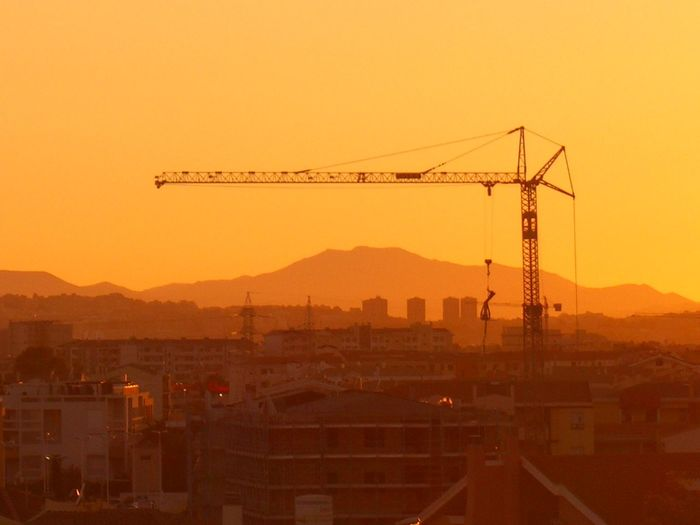 Silhouette Crane And Buildings Against Orange Sky