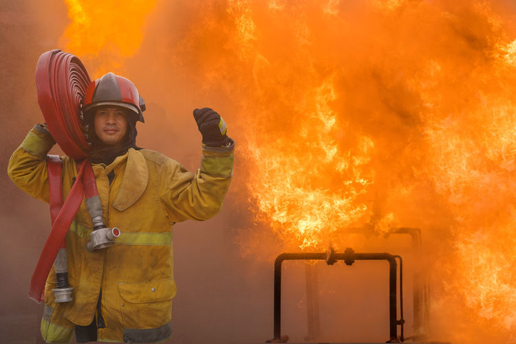 Firefighters fight the raging fire with large flames burning gas leaking.