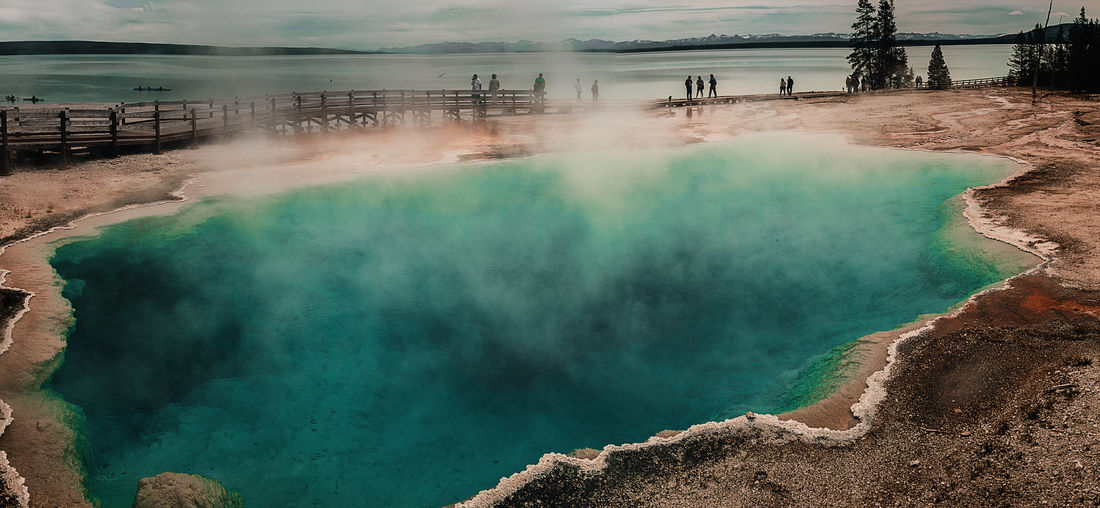 Scenic view of hot springs at yellowstone national park against cloudy sky