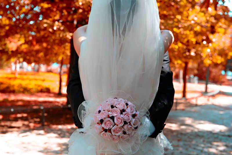 Rear View Of Bride Embracing Groom With Bouquet On Field