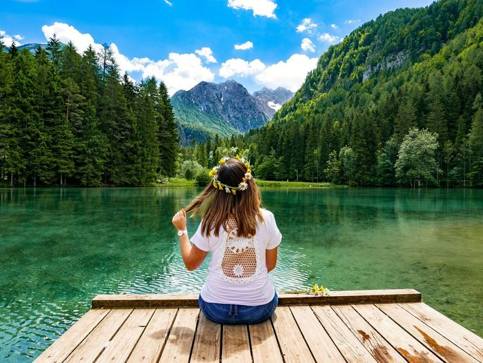 Rear view of woman sitting on pier at lake against mountains