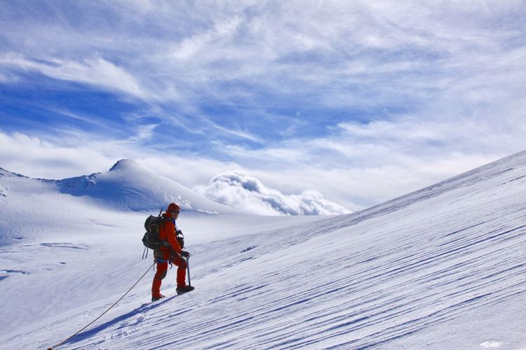 Man climbing on snowcapped mountain against sky