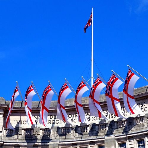 Proudly British. Royal Navy white ensign blowing in the wind with perfect synchronicity on Admiralty Arch, London. The pride of the British Navy. Britain LONDON❤ United Kingdom Flag Windy Pride Proud Heritage Building Flag Pole Tourism History Navy Ensign Admiralty Arch  Strength And Courage Summer Strong Army Royal Navy White Ensign