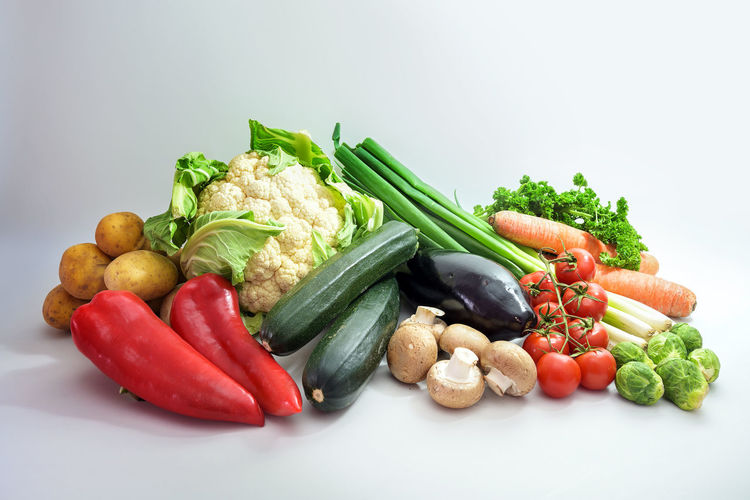 Close-up of bell peppers and vegetables on white background