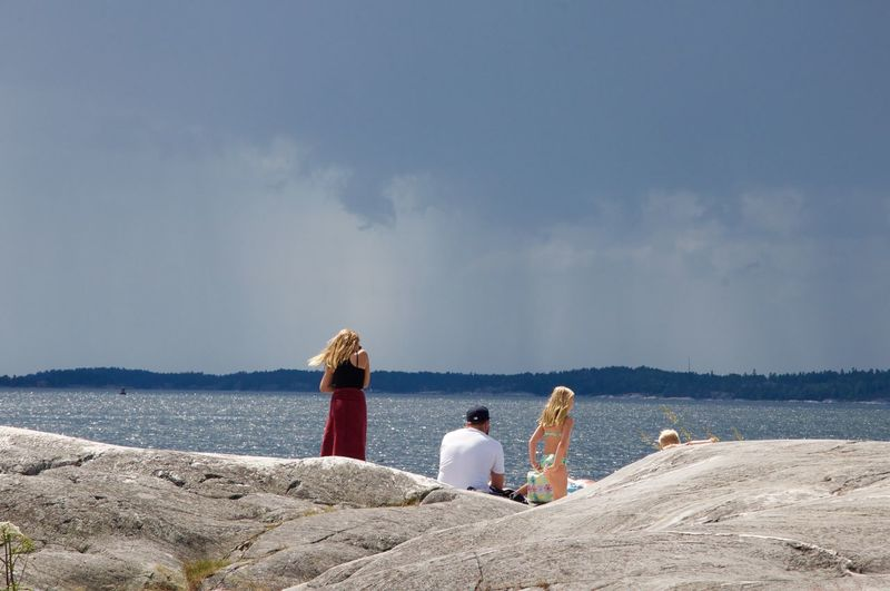 Rear view of family on rocks by sea