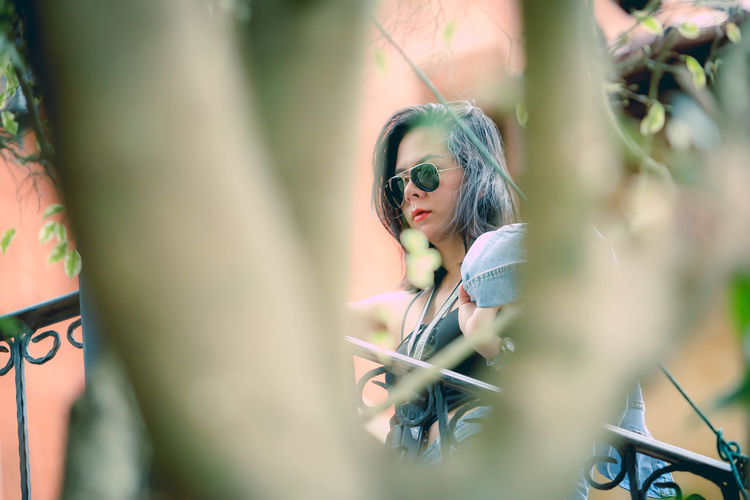 Low Angle View Of Woman Wearing Sunglasses Seen Through Branches