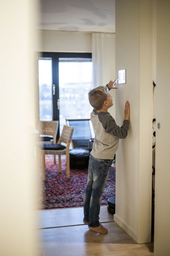 Rear view of boy standing against door at home