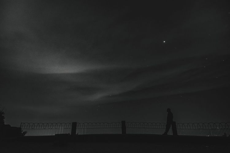 Silhouette person standing on bridge against sky at night