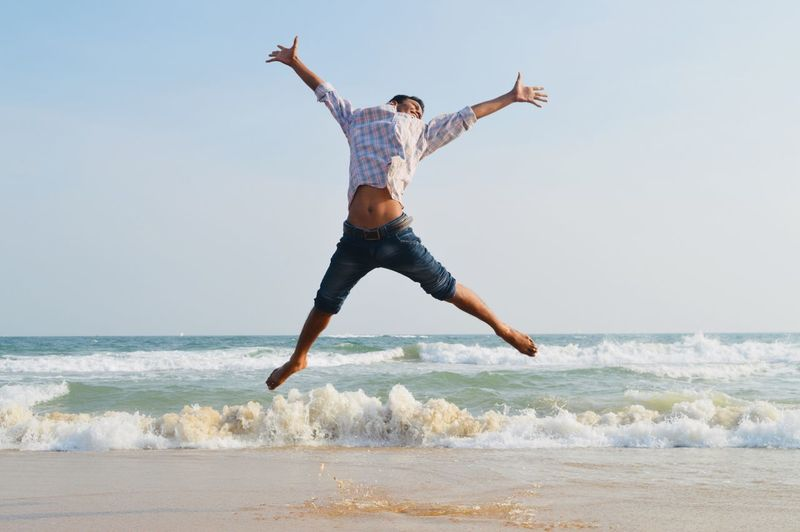 Full length of young man jumping at beach against sky