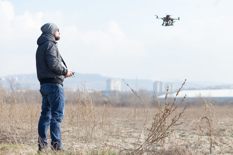 Side View Of Mid Adult Man Flying Drone While Standing On Field Against Sky