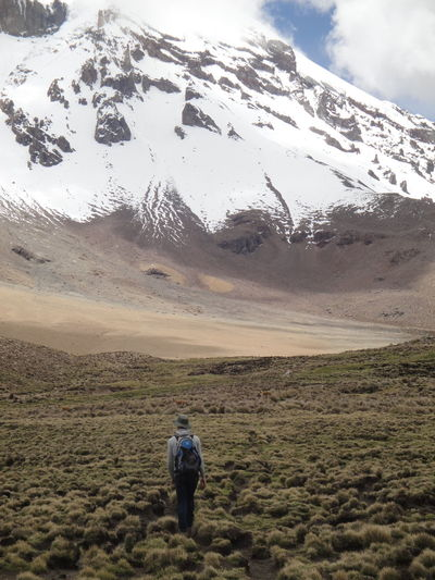 Rear View Of Woman Walking Towards Snowcapped Mountain During Winter