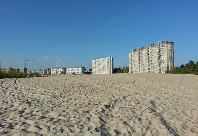 Panoramic view of beach and buildings against clear blue sky