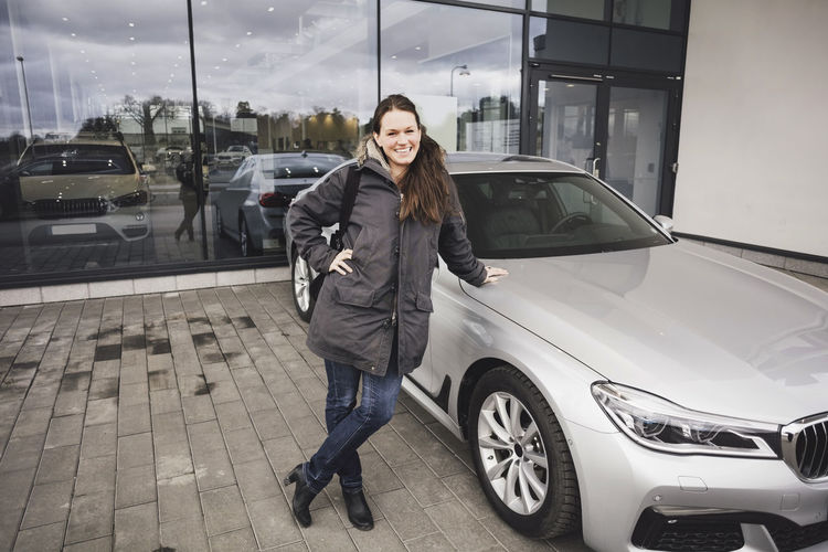 Portrait of smiling young woman standing on car