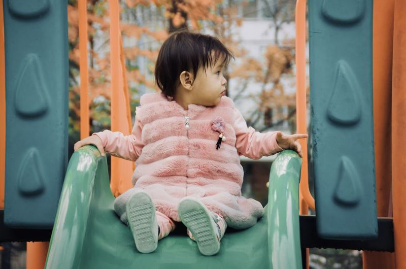 Full length of cute girl sitting on slide