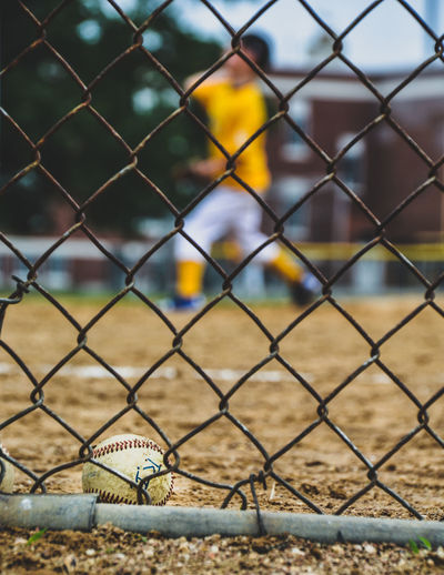 Close-up of baseball seen through chainlink fence