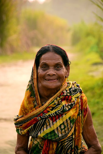 Portrait of smiling senior woman wearing sari standing outdoors