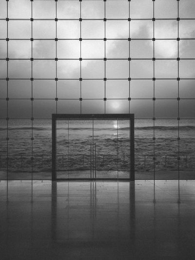 Digital composite image of wall and sea against sky