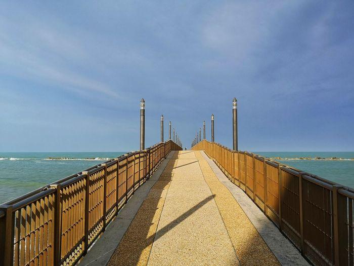 Walkway by sea against sky