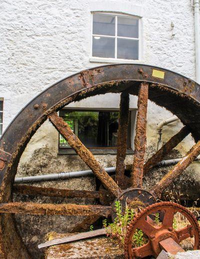 Rusty water wheel against building